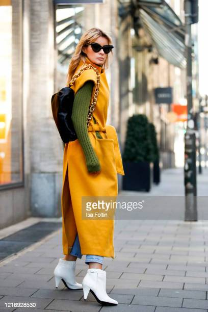 Influencer Gitta Banko, wearing a yellow sleeveless coat with cut out details by Liviana Conti, a green cashmere pullover by Boscana, a blue Jeans by...