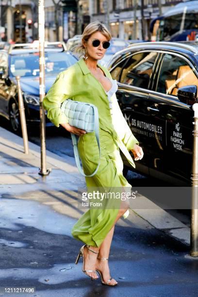 Influencer Gitta Banko wearing all over look by Zara: green skirt and blouse, light blue bra, golden sandals by Nicholas Kirkwood, a topas blue...