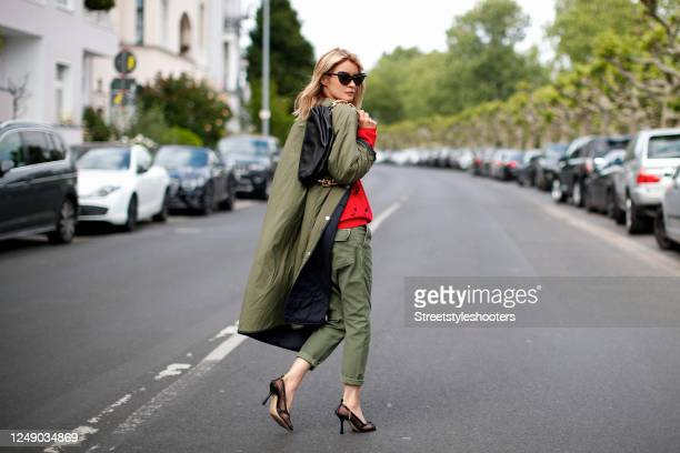 Influencer Gitta Banko, wearing an olive green long and light coat by G-Lab, a red knitted pullover with black font by Jacob Lee, olive green slouchy...