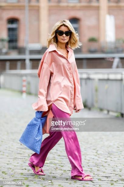 Influencer Gitta Banko wearing an orange oversized blouse by Gitta Banko, pink silk pants by Nanushka, pink silk sandals by Nanushka, indigo colored...