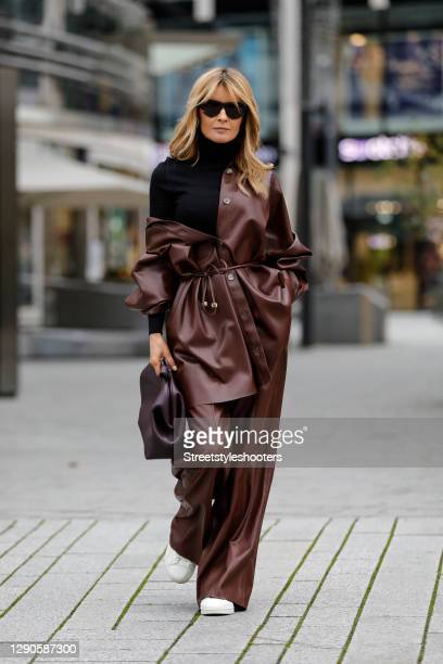 Influencer Gitta Banko wearing an oversize chocolate brown vegan leather blouse and matching pants by Nanushka, a black turtleneck pullover by Saint...
