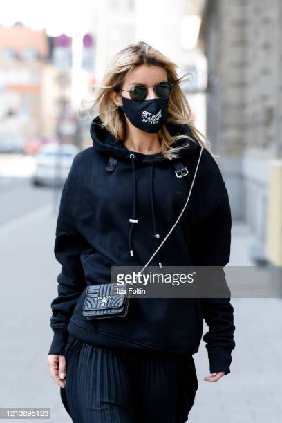 Influencer Gitta Banko wearing an oversized black hoodie by Jacob Lee a black silk pleated skirt by Boscana a black micro leather bag by Prada...