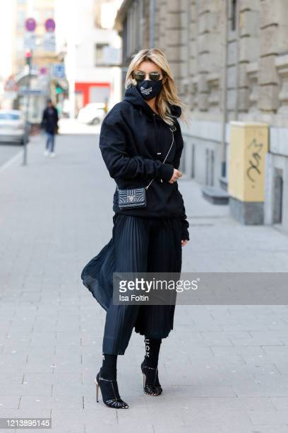 "Influencer Gitta Banko, wearing an oversized black hoodie by Jacob Lee, a black silk pleated skirt by Boscana, black socks with ""fuck off"" print by..."
