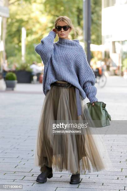 Influencer Gitta Banko wearing an oversized bluegrey knitted pullover by Isabel Marant a grey maxi tulle skirt with a black leather belt by Brunello...