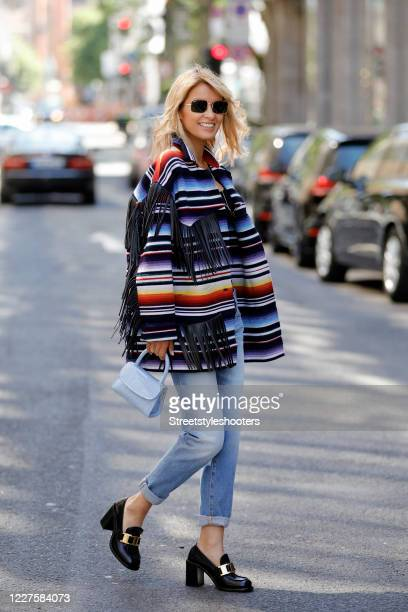 Influencer Gitta Banko wearing an oversized multicolored cashmere mix jacket with leather fringe by Alanui a snake necklace by Seelenschwester a...