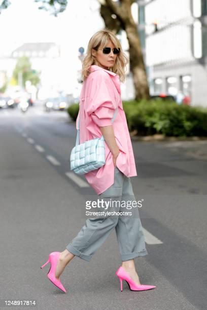 Influencer Gitta Banko, wearing an oversized pink blouse by Steffen Schraut, grey cargo pants by Seductive, a light blue padded casette bag by...