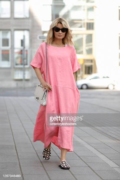 Influencer Gitta Banko wearing an oversized pink maxi dress by Gitta Banko, black flats with crystals by Alexander McQueen, a silver bag by Chanel...