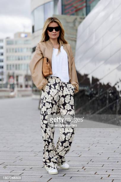 Influencer Gitta Banko wearing beige leather jacket by Dorothee Schumacher, a white t-shirt by Juvia, dark grey pants with cream colored flower print...