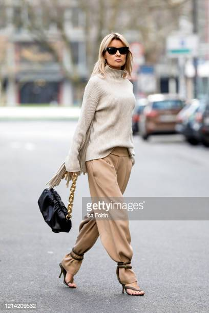 Influencer Gitta Banko wearing beige pants and a beige fringed turtleneck sweater by Liviana Conti wrapped python sandals and a black chain pouch bag...