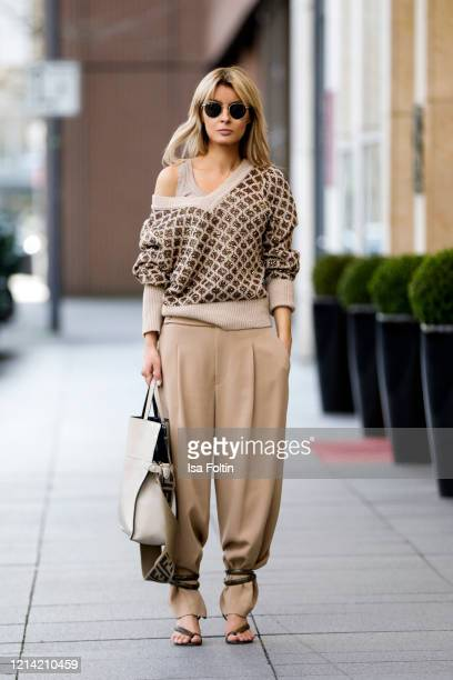 Influencer Gitta Banko wearing beige pants and a beige swaeter with a brown check pattern with sequins by Liviana Conti wrapped python sandals by...