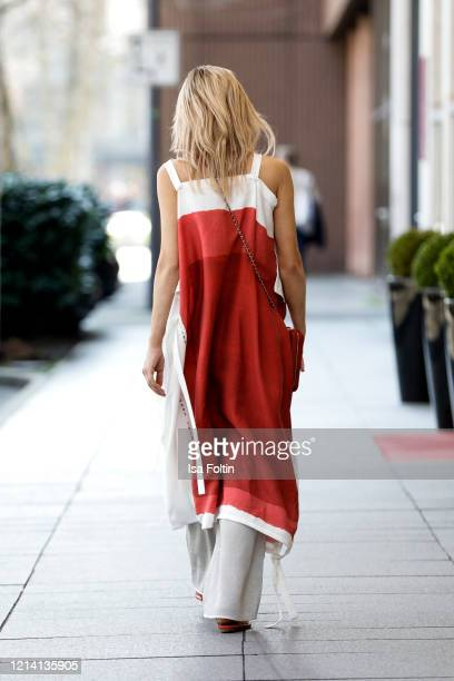 Influencer Gitta Banko wearing beige pants and a redwhite dress with geometric pattern by Annette Goertz a red cell phone bag by Chanel flat red...