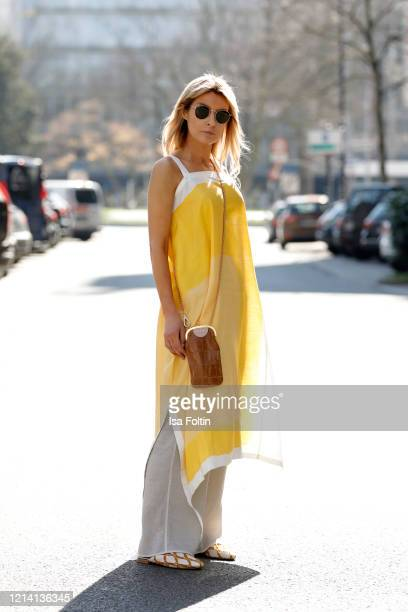 Influencer Gitta Banko wearing beige pants and a yellowwhite dress with geometric pattern by Annette Goertz a brown cell phone bag by Marni shoes by...