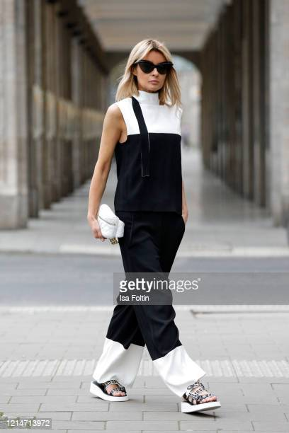 Influencer Gitta Banko, wearing black and white pants and a black and white shirt by Annette Goertz, flat sandals by Chanel, a white leather bag by...