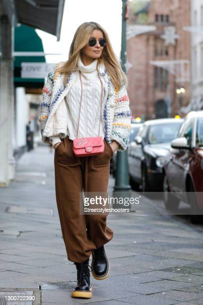 Influencer Gitta Banko wearing black boots with beige soles 'The bounce boots' by Bottega Veneta, a white oversize cardigan with multicolored stripes...