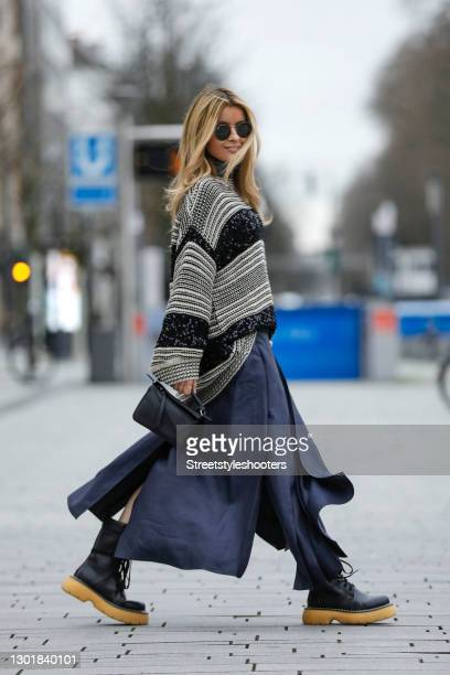 Influencer Gitta Banko wearing black boots with beige soles 'The bounce boots' by Bottega Veneta, a black an white striped pullover with sequin...