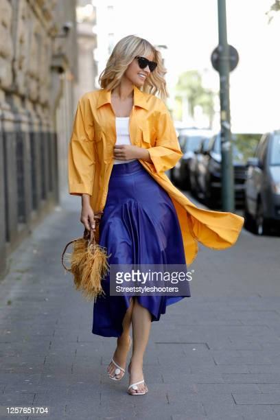 Influencer Gitta Banko wearing cream colored toe sandals by Coperni, a dark blue leather skirt by Topshop, sunglasses by Bottega Veneta, a white tank...