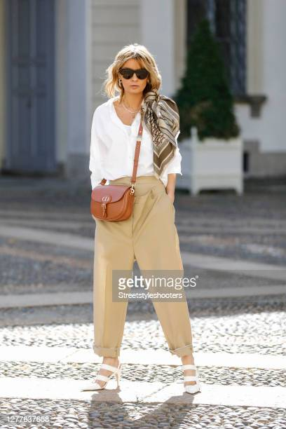 Influencer Gitta Banko, wearing double waist pants by Burberry, a scarf by Dior, a brown bobby bag by Dior, sunglasses by Bottega Veneta and white...