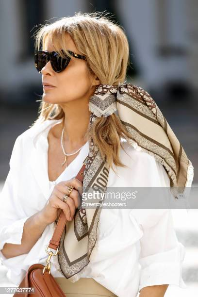 Influencer Gitta Banko, wearing double waist pants by Burberry, a scarf by Dior, a brown bobby bag by Dior and sunglasses by Bottega Veneta is seen...