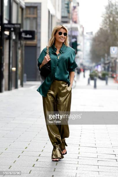Influencer Gitta Banko, wearing golden silk pants by Liviana Conti, an oversized green blouse by Liviana Conti, black sandals by Bottega Veneta, a...