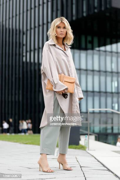 Influencer Gitta Banko wearing grey pants by The Frankie Shop, a beige oversized blouse by Gitta Banko, a caramel colored clutch by Hermes, beige...