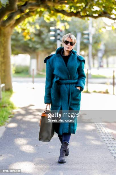 Influencer Gitta Banko, wearing petrol green coat by Boscana, a jeans by Citizens of Humanity, a black pullover by Boscana, a khaki colored peekaboo...