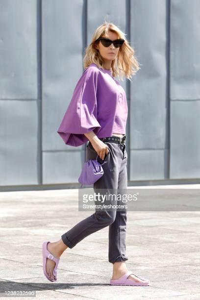 Influencer Gitta Banko, wearing purple sandals by Birkenstock, a purple mini pouch bag by Bottega Veneta, sunglasses by Mykita x Maison Margiela, an...