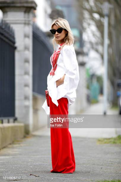 Influencer Gitta Banko wearing red pants by Boscana a long white blouse with a red print by Annette Goertz a red cell phone bag by Chanel red sandals...