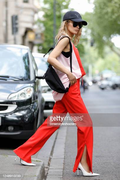 Influencer Gitta Banko wearing red sweatpants with a slit on both sides by Y-3, a red and pastel pink tank top by Y-3, a black bag by Marcela, a...