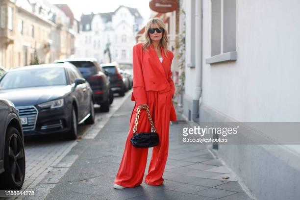 Influencer Gitta Banko wearing red-orange high waist wool blend pants and a matching blazer by Materiel Tbilisi, a white tank top by Zara, white...