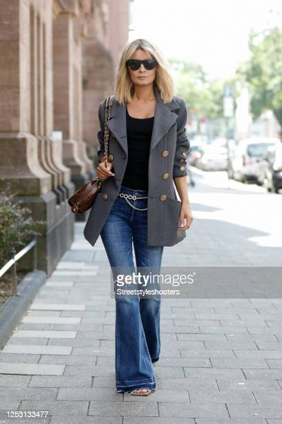Influencer Gitta Banko wearing sunglasses by Bottega Veneta, a black tank top by Zara, a grey oversized Blazer by Chanel, a gold chain belt with...