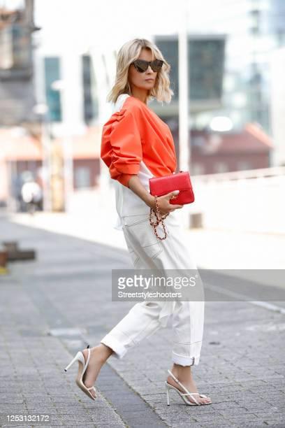 Influencer Gitta Banko wearing sunglasses by Bottega Veneta, white denim jeans by Marni, cream colored open toe sandals by Coperni, a white and...