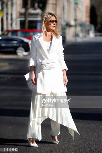 Influencer Gitta Banko, wearing white blazer and a white pleated skirt by Liviana Conti, white pants by The Mercer, a white tanktop by Zara, white...
