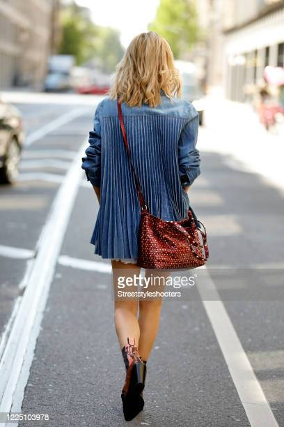 Influencer Gitta Banko wearing white denim shorts by True Religion a black tank top by iheart a denim blazer with a pleated back by Red Valentino...