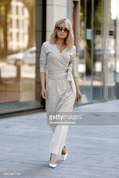 Influencer Gitta Banko wearing white knitted pants by Zoe Ona a beige wrap dress by Zoe Ona white leather pumps by Balenciaga sunglasses by Marc...