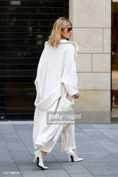 Influencer Gitta Banko wearing white knitted pants by Zoe Ona a beige wrap dress by Zoe Ona an oversized white coat by Boscana white leather pumps by...