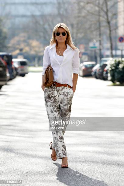 Influencer Gitta Banko, wearing white pants with jungle prints by Seductive, a double belt by Boscana, a white blouse by Steffen Schraut, sandals by...