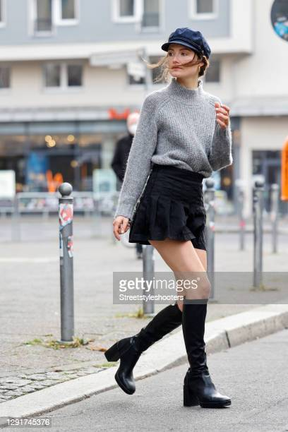 Influencer Hannah Mueller-Hillebrand alias @Namastehannah wearing black knee high boots by Pull and Bear, a black mini pleated skater skirt by Brandy...