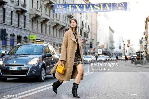Influencer Jacqueline Zelwis wearing a beige coat by Lala Berlin an animal printed dress by Lala Berlin black boots by Fendi and a dark yellow bag by...