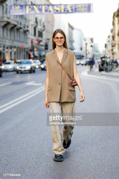 Influencer Jacqueline Zelwis, wearing a beige vest by Munthe, beige pants by Holzweiler, black sneakers by Balenciaga, a brown bag by Boyy and...