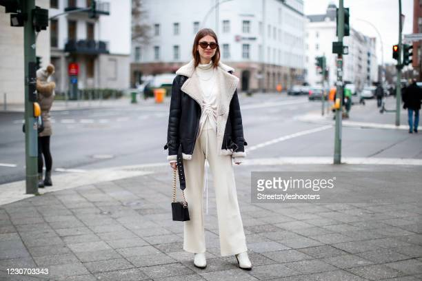 Influencer Jacqueline Zelwis wearing a black leather jacket with cream colored faux fur lining and collar by Hiso, cream colored wide leg pants by...