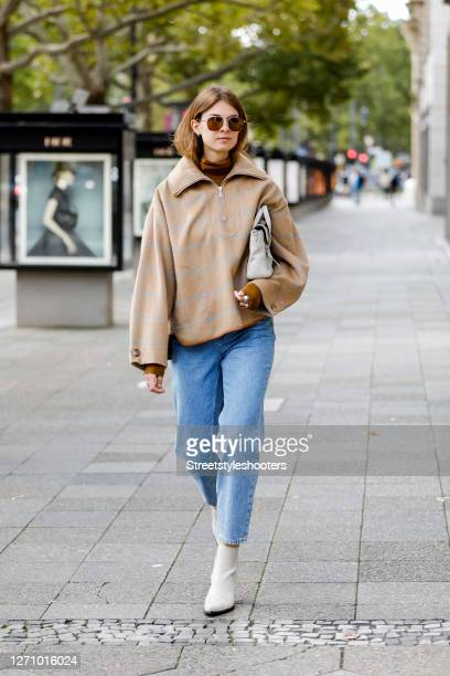 Influencer Jacqueline Zelwis wearing a brown turtleneck sweater by Samsoe Samsoe, a light brown Jacket with light grey stripes and a blue Jenas by...