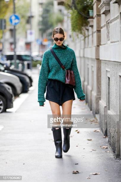 Inflöuencer Jacqueline Zelwis wearing a green pullover by Sportmax black shorts by Onbekends black kneehigh rubber boots by Hunter a dark purple bag...