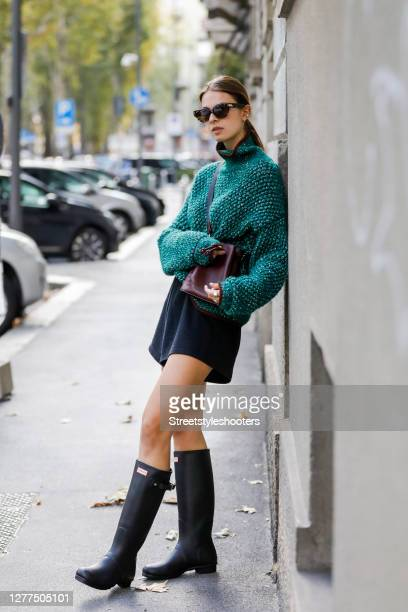 Inflöuencer Jacqueline Zelwis, wearing a green pullover by Sportmax, black shorts by Onbekends, black knee-high rubber boots by Hunter, a dark purple...
