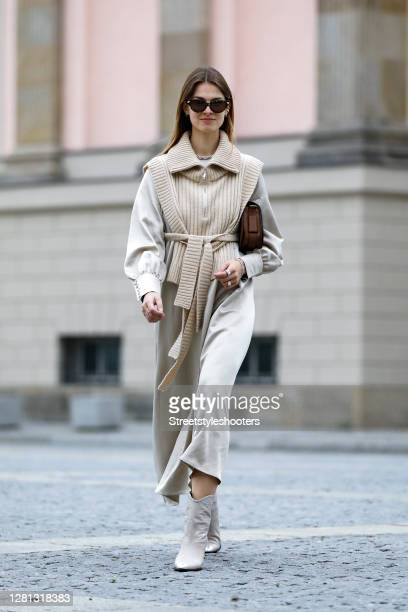 Influencer Jacqueline Zelwis, wearing a long beige dress by Black Palms the Label, a beige knitted vest by Holzweiler, beige boots with crocodile...
