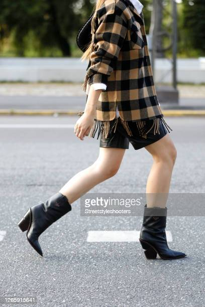 Influencer Jacqueline Zelwis wearing a yellow black checked jacket with fringes by Sandro a white blouse by Gestuz black cowboy boots by Fendi and a...