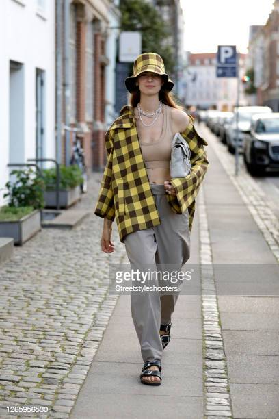 Influencer Jacqueline Zelwis, wearing a yellow black checked jacket and hat by Baum und Pferdegarten, a crop top by Zara, grey pants by Inwear, a bag...