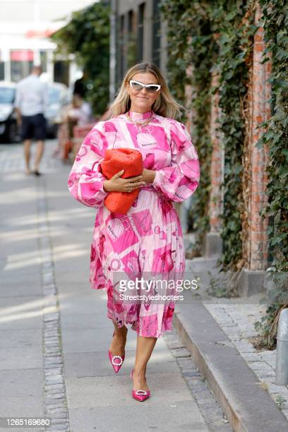 Influencer Janka Polliani, wearing a pink rose colored dress with fashion applications by Balenciaga, a red bag by Bottega Veneta and pink sandlas by...