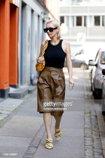 Influencer Justyna Czerniak, wearing a black top by Toteme, short brown leather pants by The Frankie Shop, beige mules by Bottega Veneta and a orange...