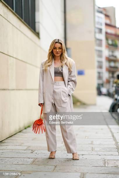 "Influencer Karolina Wójcik ""VIVA_A_VIVA"" wears sunglasses, a white oversized blazer jacket, a gray wool cropped top, white large pants, an orange bag..."