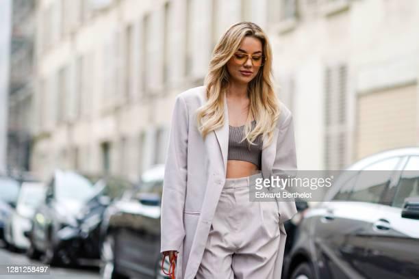 "Influencer Karolina Wójcik ""VIVA_A_VIVA"" wears sunglasses, a white oversized blazer jacket, a gray wool cropped top, white large pants, outside..."